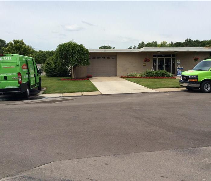 Two SERVPRO trucks parked in front of a building