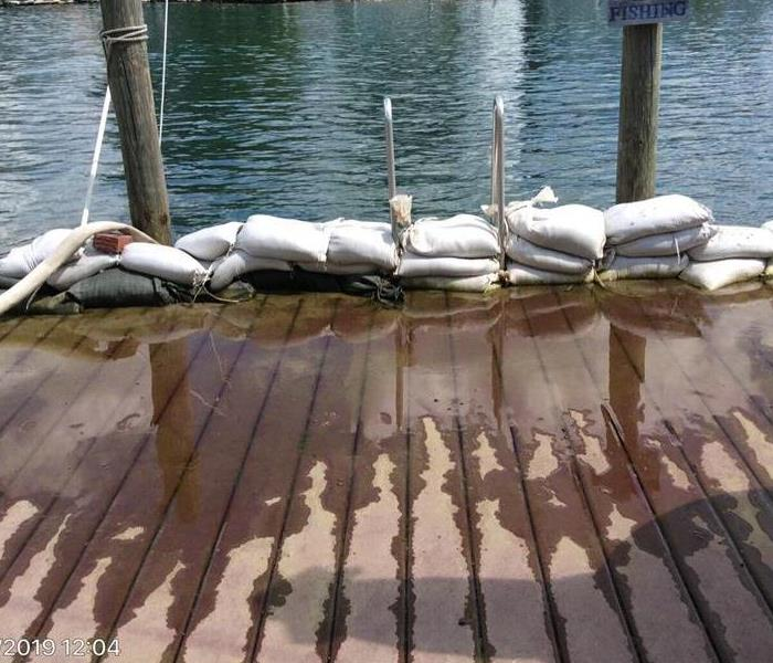 Sand bags lined up on a wet dock of a St Clair County home. River level is at same height as the dock.